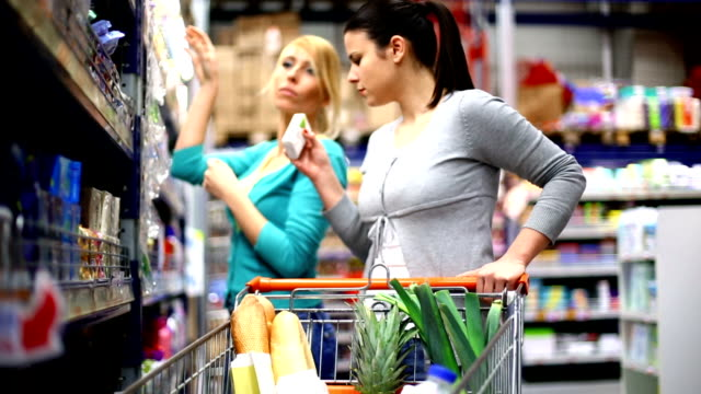Two women buying cosmetics in supermarket.