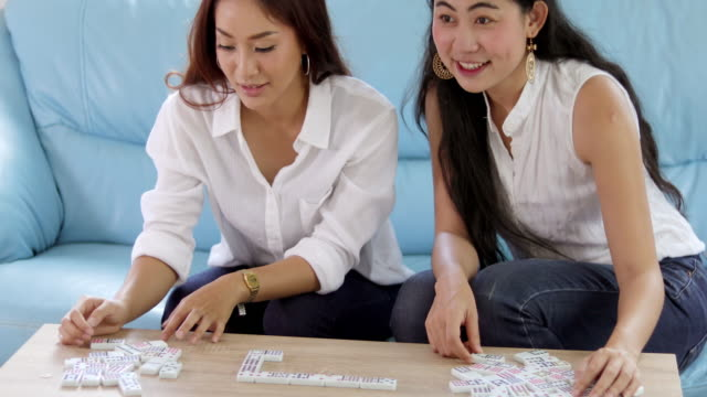 Two women Competitive friends playing Domino's games and excited happy cheerful at home