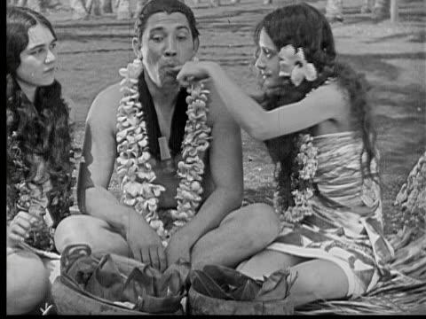 1934 B/W MS Two women feeding man, stuffing food into his mouth / Hawaii, USA