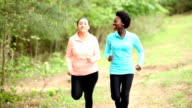 Two women friends running in neighborhood park.
