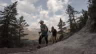 Two women hiking up alpine trail