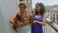 CU, ZO, ZI, Two women holding barking dachshunds on balcony, Old Havana, Cuba