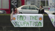 WS Two women holding End the Occupation sign over canal, County Maigh Eo, Connacht, Ireland