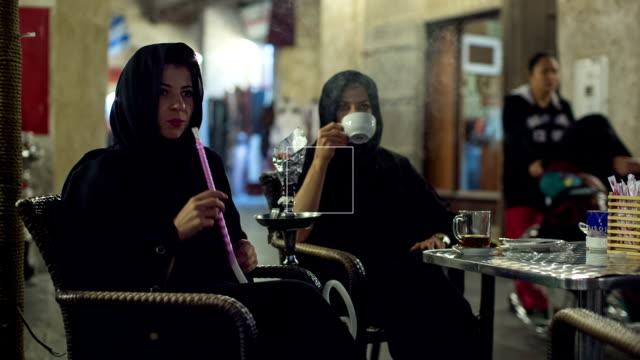 Two women in abayas drinking coffee and smoking hookah at the Arabian market Souq Waqif in Doha, Qatar