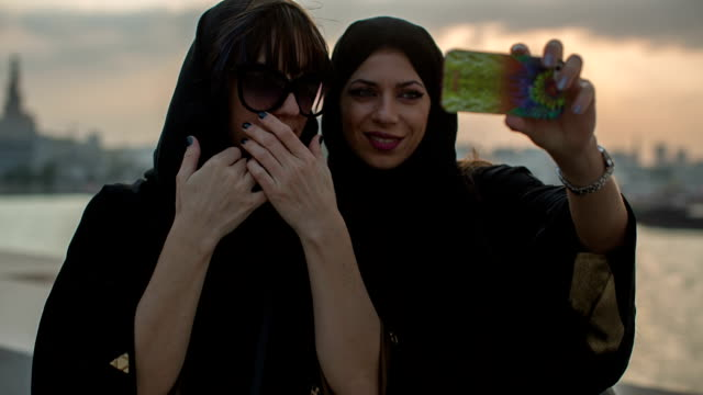 Two women in abayas make selfies in front of the Museum of Islamic Art in Doha, Qatar