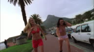 Two women in bikini tops and shorts rollerblading along sidewalk, Camps Bay, South Africa Available in HD.