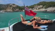 WS PAN Two women in bikinis relaxing on deck of Luxury Yacht / Portals Nous, Mallorca, Spain