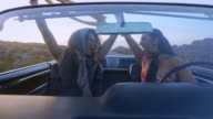 Two women in classic convertible throw hands in air and cheer and let scarf blow in wind on road trip to Vegas.