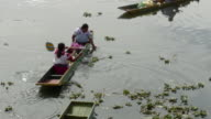 HA ZO WS Two women in traditional dresses paddling in waterways / Patzcuaro, Michoacan, Mexico
