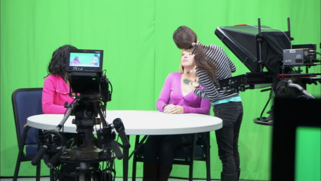 MS ZI Two women in TV studio having make-up done, Brooklyn, New York City, USA