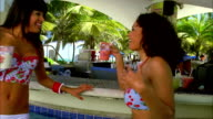 Two women laugh and dance in a swimming pool. Available in HD.