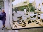 1962 two women looking in shoe store display window then entering store / industrial