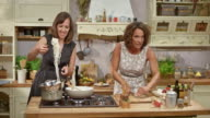 Two women making a stir fry on a cooking show in a rustic kitchen