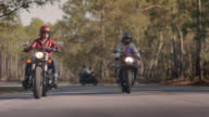 SLO MO. Two women on motorcycles drive down forest highway as another biker rides past.