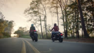 SLO MO. Two women on motorcycles travel down coastal highway at sunset.