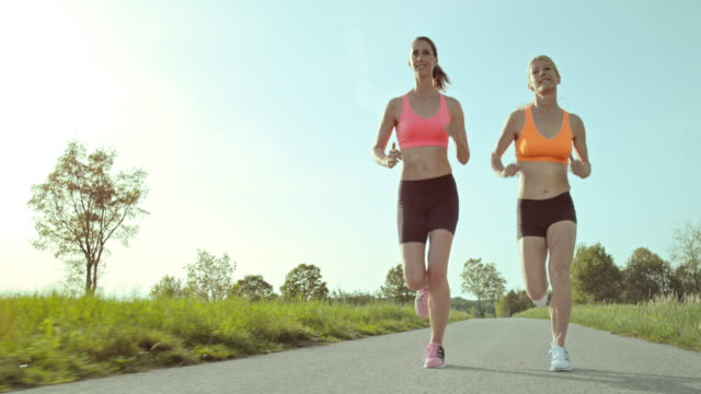 SLO MO TS Two women on their run through countryside