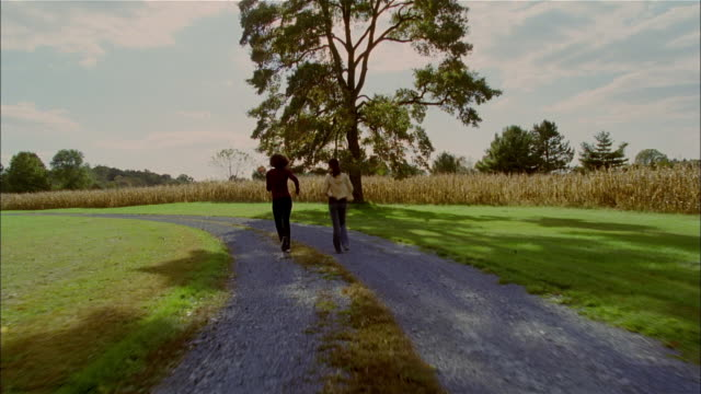 WS, two women power walking on country road, rear view, USA, Pennsylvania, Solebury