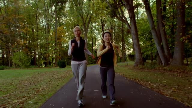 Two women power walking on park footpath