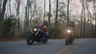 SLO MO. Two women riding motorcycles side by side laugh together and cruise down secluded forest highway.