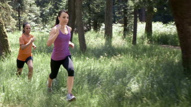 SLO MO DS Two women running through a forest