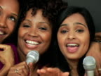 CU Two women singing into karaoke microphone, smiling / New York City, New York, USA