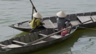 MS Two women sitting in small boats by riverside / Hoi An, Quang Nam, Viet Nam