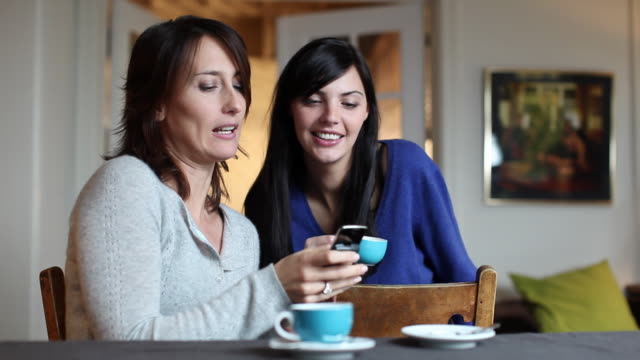 MS R/F Two women talking and showing photos on mobile phone sitting at dining table / Brussels, Brabant, Belgium