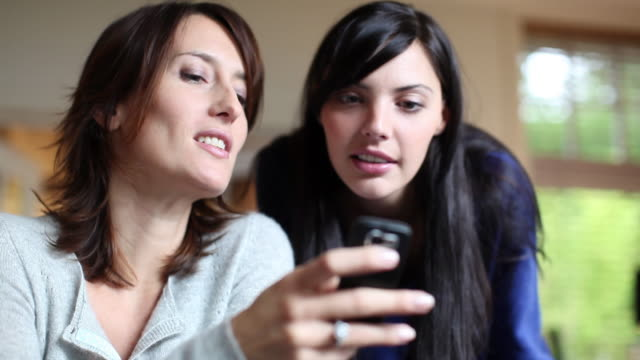 CU R/F Two women talking and showing photos on mobile phone sitting at dining table / Brussels, Brabant, Belgium