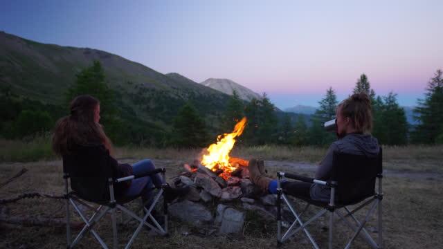 Two women talking by campfire