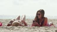 WS Two women text messaging on beach / South Beach, Miami, Florida, USA