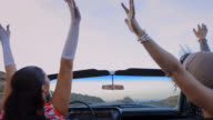 MS. Two women throws hands in air and laugh in classic convertible on desert highway.
