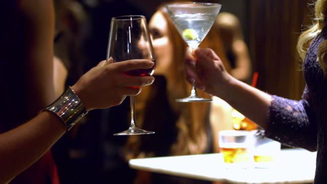 CU two women toasting alcoholic drinks