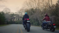 SLO MO. Two women travel down empty forest road on motorcycles.