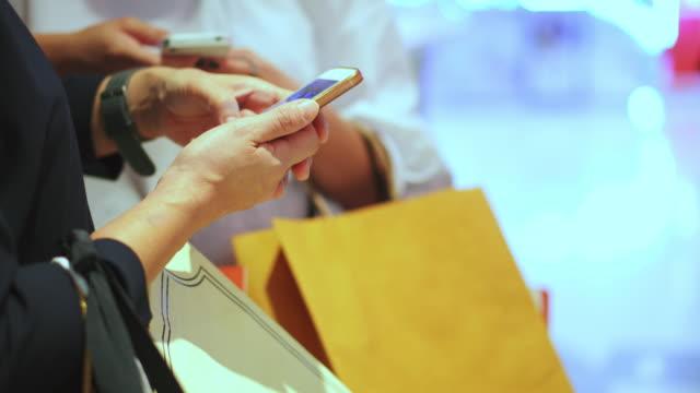 Två kvinnor som använder smartphone i köpcentrum