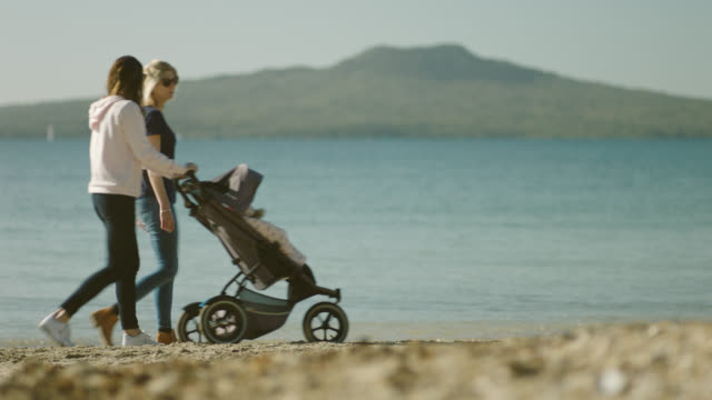 Two women walking along beach with stroller