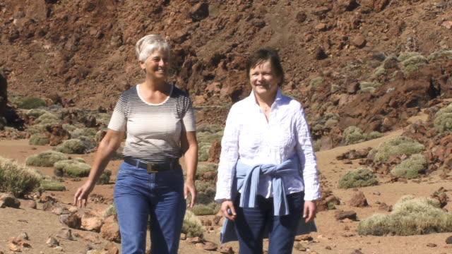 MS, ZO, two women walking at foot of mountain, Mount Teide, Tenerife, Canary Islands, Spain