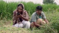 Two women watching mobile phone in the farm, Haryana, India