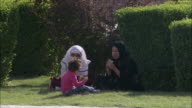 MS Two women with girl sitting on lawn at Naghsh-e Jahan Square, Isfahan, Iran