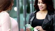 Zwei Frauen mit Einkaufstaschen und Geld