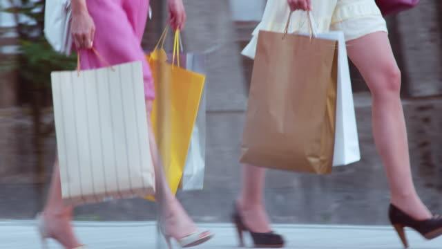 TS Two women with shopping bags crossing a bridge