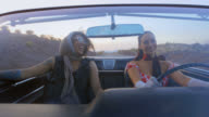 Two women with vintage style talk and laugh in classic convertible on Vegas road trip.