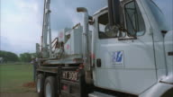 CS SLO MO WS PAN Two workers on digging truck installing pole / Johnson City, Texas, USA