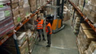 Two workers talking about the redistribution in the warehouse