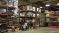 Two workers using forklifts in a warehouse