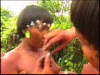 Two Yanomami Indian women apply decorations in the Amazon