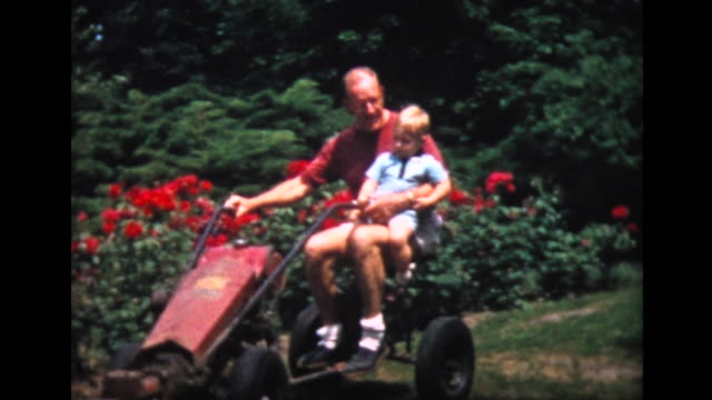 1957 two year old boy on lawn mower