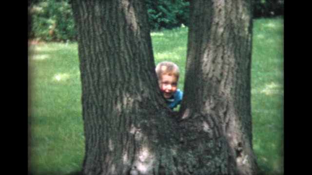 1957 two year old boy peeks out behind tree
