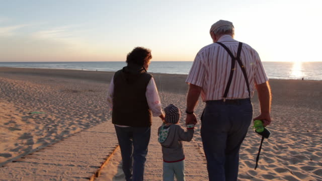 Two year old boy walking with his grandparents on the beach in Southern France.