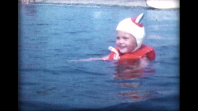 1959 two year old girl swims with life vest and funny cap
