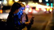 Two young adults in city play with tablet at night